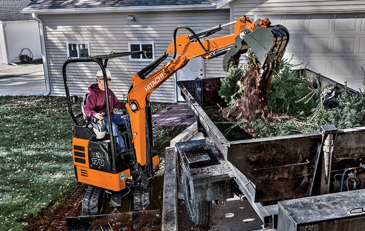 Hitachi ZX17U-5 Compact Excavator with operator in cab dumping debris