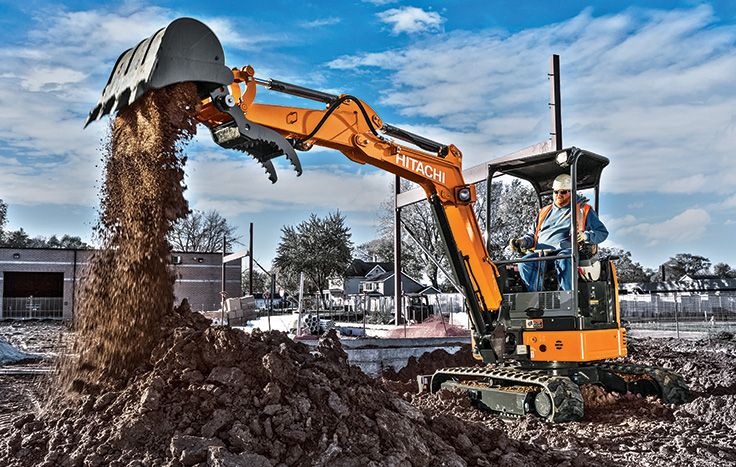 Hitachi ZX26U-5 Compact Excavator with operator in cab dumping dirt