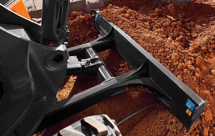 Although not a replacement for a grading tractor, standard backfill blades let this excavator fill-in quite capably.