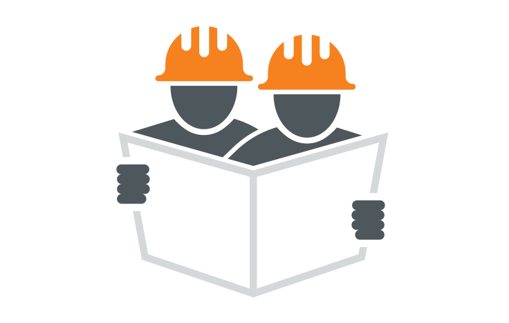 two people in hard hats looking at a paper