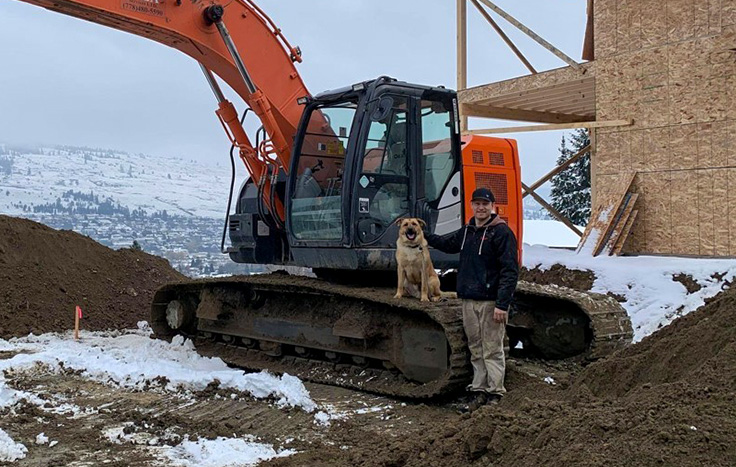 HERD member Riley Hastings with his dog, standing by his Hitachi excavator